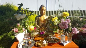 Buddha in sunshine with flowers